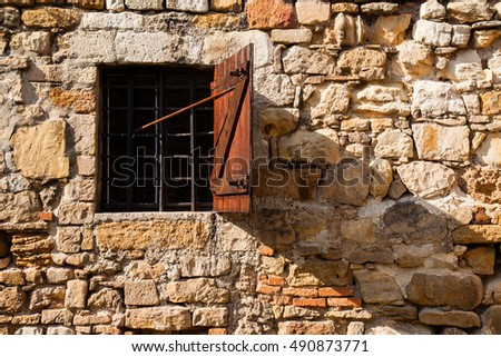 Crushed stone wall detail with a barred window