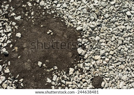 Crushed stones partly covered with new asphalt concrete. - stock photo