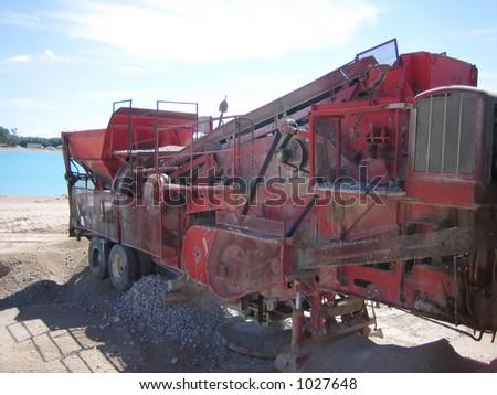 crusher pounding gravel at gravel pit (underwater gravel site) - stock photo