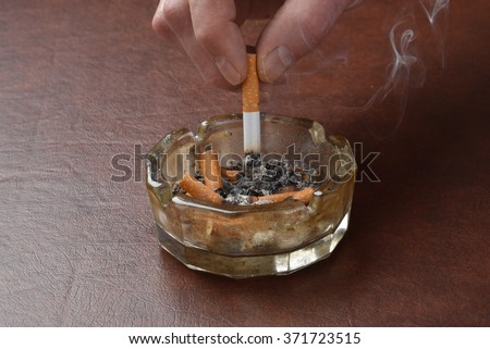 Crushing out a cigarette in a dirty ashtray - stock photo