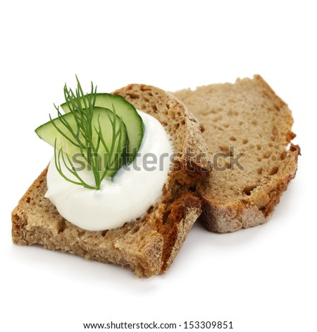 Crusty bread with cottage cheese, cucumber slices and dill on white background