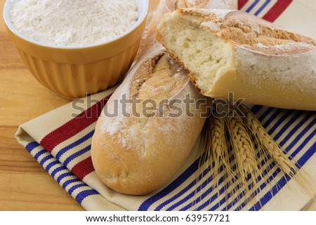 Crusty bread with flour and wheat stalks illustrate tasty food and wheat allergens - stock photo