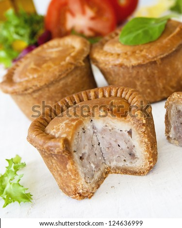 Crusty English pork pie sliced against a background of pies green leaf salad and tomatoes - stock photo