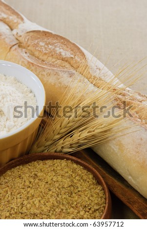 Crusty golden baguette bread with flour, wheat and wheat germ illustrate tasty food or wheat allergens with copy space.