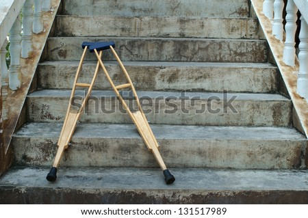crutches lay down on stair. - stock photo
