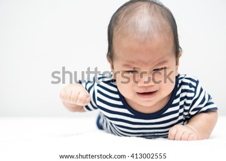 Crying Asian baby lying on stomach and raising his head - stock photo