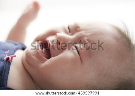 Crying asian Chinese baby girl lying on bed