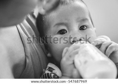 Crying Asian kid drinking breastfeeding milk from bottle after eating food