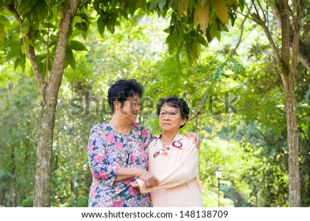 crying Asian senior mother with her senior daughter at outdoor park - stock photo