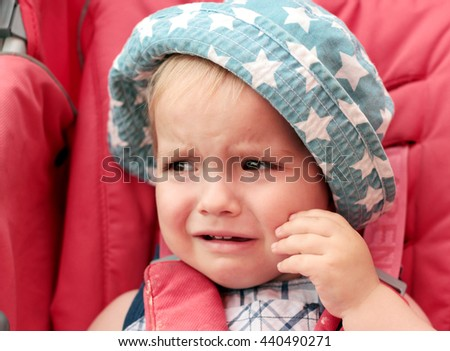 Crying baby boy wearing a summer hat in the stroller, bad mood, negative emotion concept - stock photo