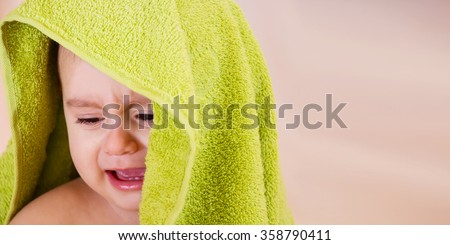 Crying baby boy with a green towel on his head - stock photo