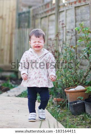 Crying baby girl in the garden, walking
