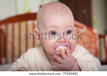 Crying baby girl lying on white towel - stock photo
