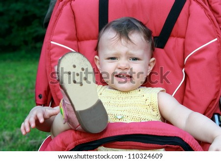 Crying baby girl sitting in stroller outdoor with holding up the leg on nature background. Closeup portrait - stock photo