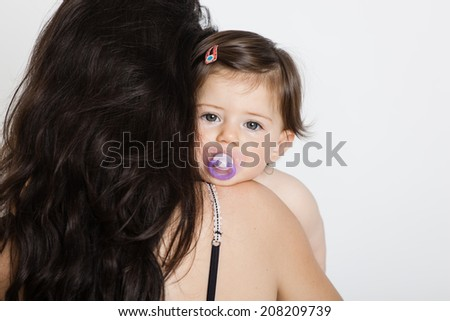 Crying baby girl with her mother isolated on white - stock photo