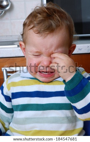 Crying baby in the kitchen.Crying child.Little child crying. - stock photo