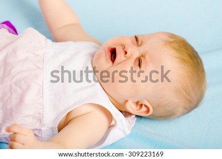 Crying baby lying on a blue plaid - stock photo