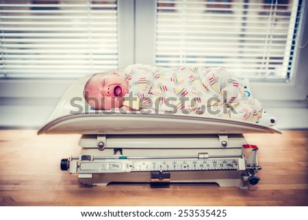 Crying Baby on a Retro Weight Scale - stock photo