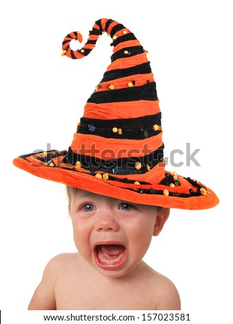Crying baby, wearing a Halloween witch hat.