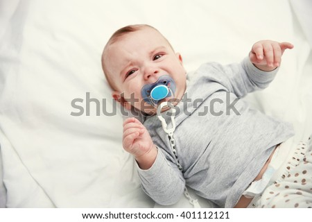 Crying baby with dummy lying on soft bed, close up - stock photo