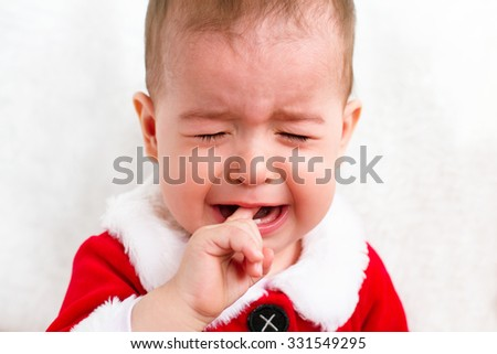 Crying beautiful Christmas toddler with a finger in mouth on white background - stock photo