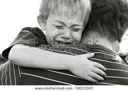 Crying Boy being comforted by his father - stock photo