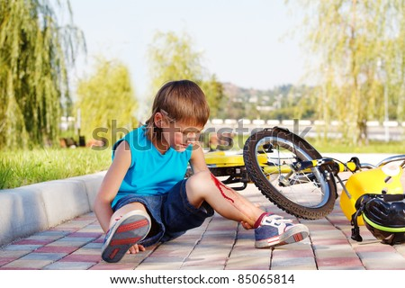 Crying boy with a bleeding injury sitting beside the bike that he has fallen from - stock photo