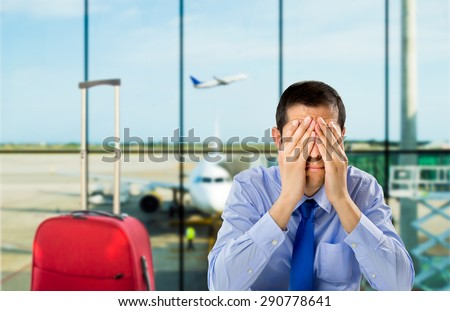crying businessman who delayed flight at an airport - stock photo