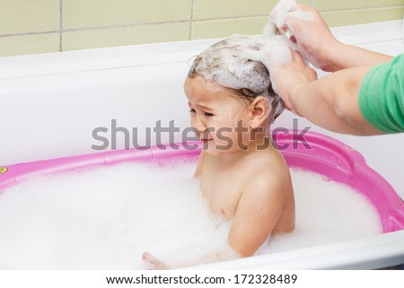 Crying child during bathing and washing hair. - stock photo
