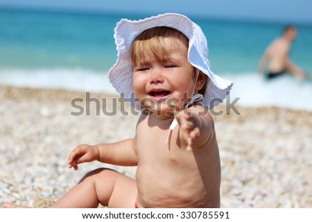 Crying child stretching her hand to ask a help, summer outdoor - stock photo