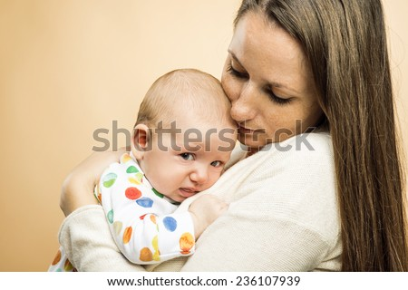 Crying child with mother studio shot on beige background - stock photo