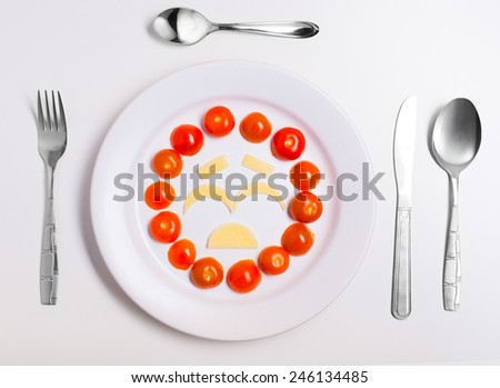 crying emoticon food, made from cheese and tomatoes, on a plate with cutlery, isolated