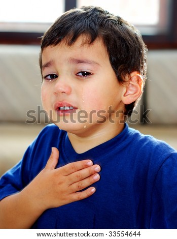Crying emotional kid with tears on his cheeks and hand on the chest - stock photo