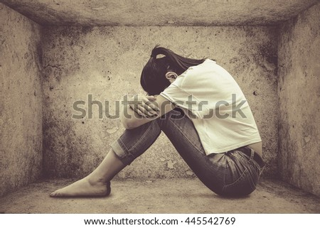 crying girl hug her knee and sitting alone in empty room (vintage tone)