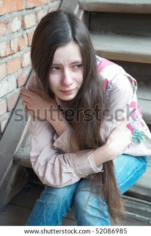 Crying girl with tears sitting on wooden stairs near red brick wall - stock photo
