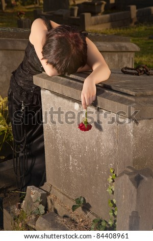 Crying gothic girl leaning on a tombstone holding a rose - stock photo