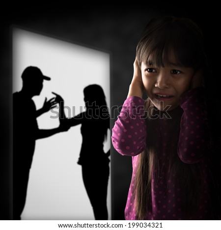 Crying illtle asian girl with her fighting parents in the background - stock photo