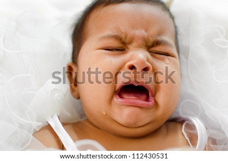 Crying Indian baby girl lying on bed - stock photo