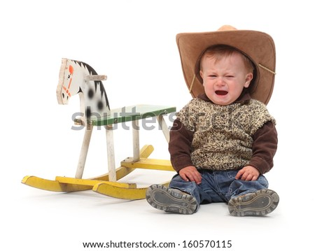Crying kid after accident on a rocking horse. - stock photo