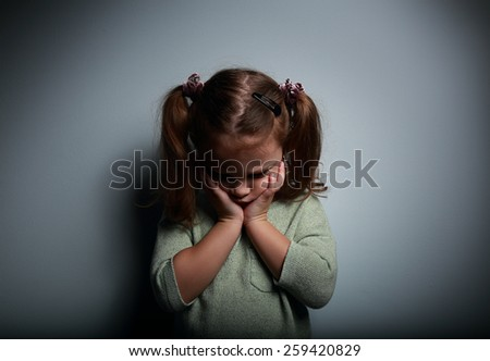 Crying kid girl holding the face the hands and looking down on dark background - stock photo