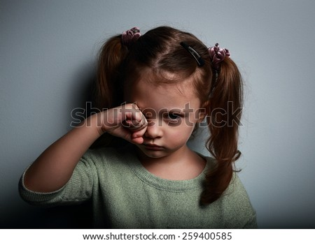 Crying kid girl with hand near eyes looking unhappy on dark background - stock photo