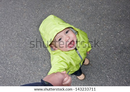 crying kid on the street by a hand with the father - stock photo