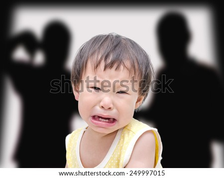 Crying little asian girl with her fighting parents in the background - stock photo