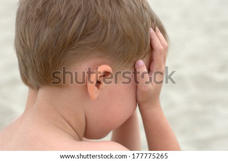 crying little boy closing face with his hands - stock photo