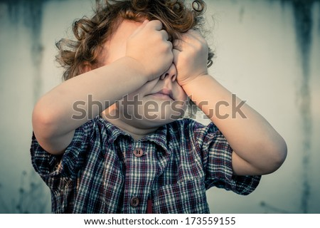 crying little boy covers his face - stock photo