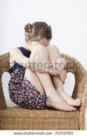 crying  little girl nine years old sitting on chair - stock photo