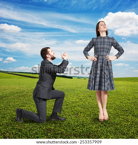 crying man looking at beautiful woman and asking for forgiveness. photo at outdoor