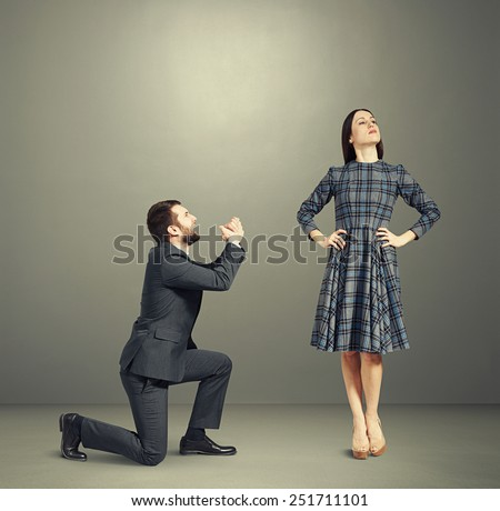 crying man looking at young beautiful woman and asking for forgiveness. photo over dark background - stock photo