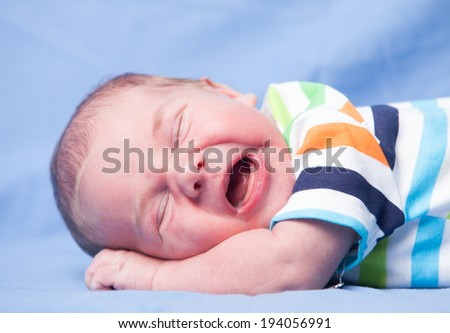 Crying newborn baby boy lays on his stomach - stock photo