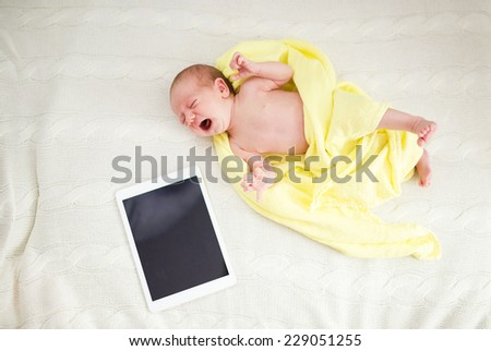 Crying newborn baby girl lying on bed next to digital tablet - stock photo